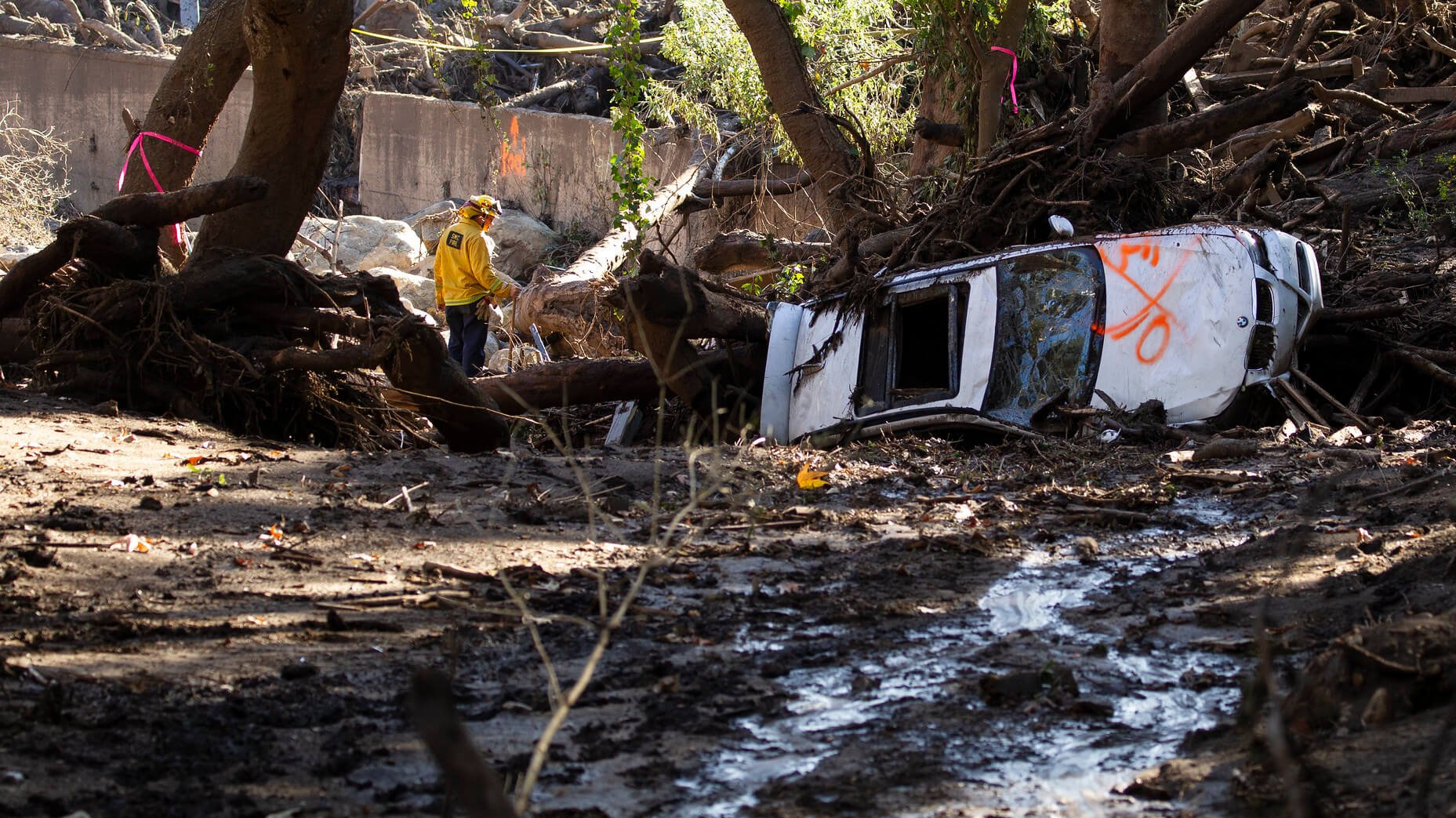 A car is overturned and a neighborhood overrun with mud as first responders and soldiers from the 315th Vertical Construction Company, California Army National Guard, work to clear debris, Jan. 13, 2018, in Montecito, California.